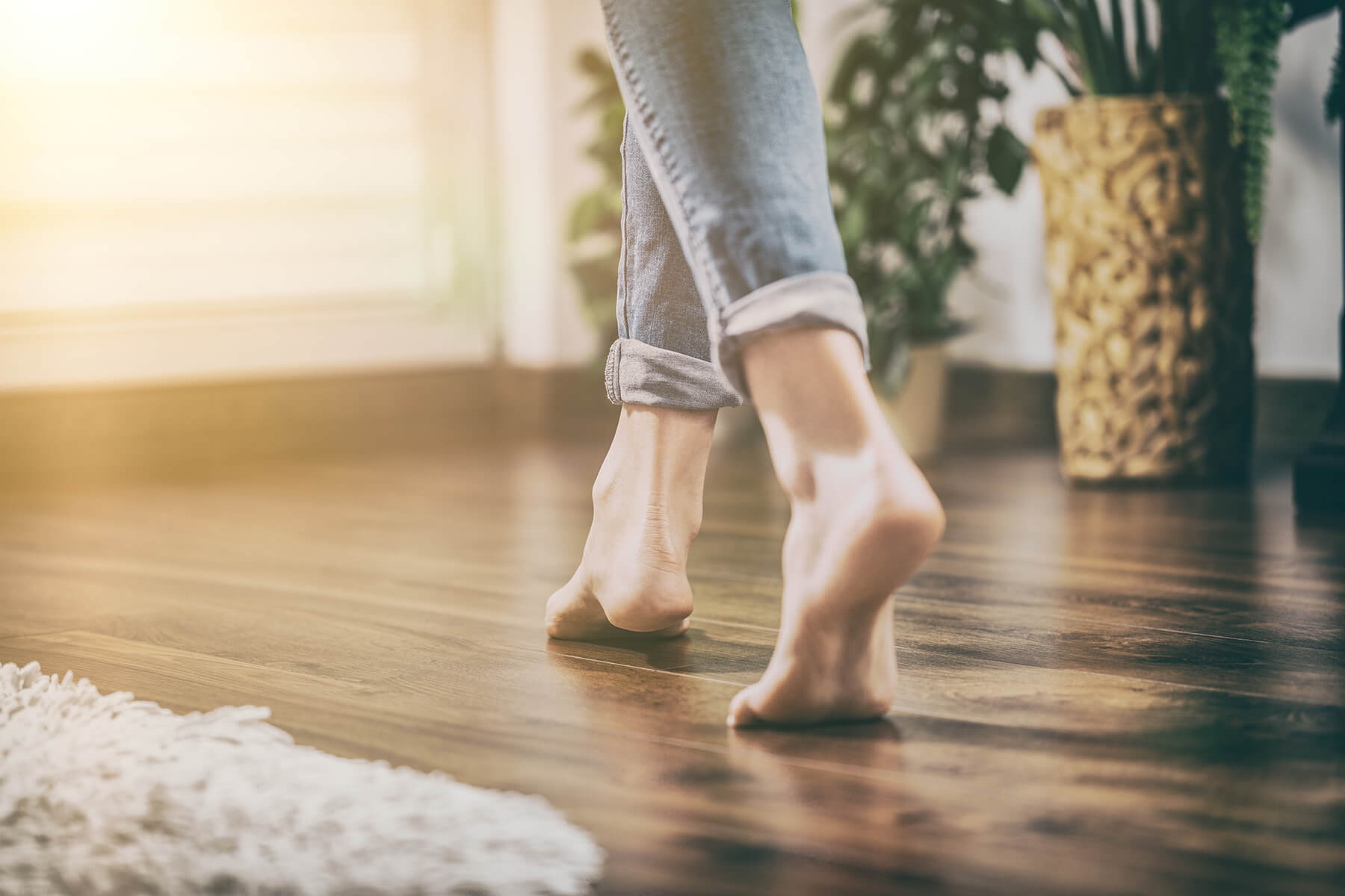 Woman walking across a hardwood floor